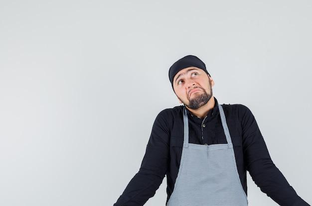Мужчина-повар показывает беспомощный жест в рубашке, фартуке и выглядит смущенным. передний план.