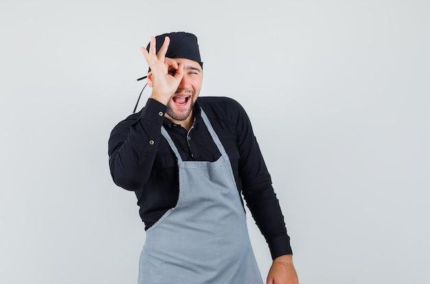 Повар-мужчина показывает знак ок на глазу в рубашке, фартуке и выглядит удивленным. передний план.