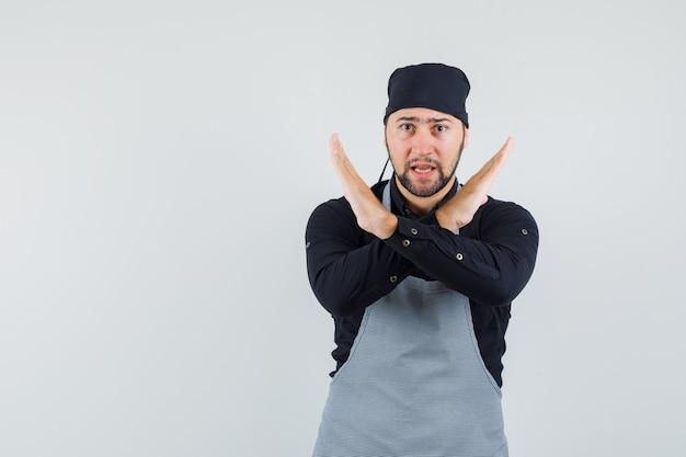 Повар-мужчина показывает жест стоп в рубашке, фартуке и выглядит строго, вид спереди.