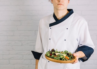 Male cook standing with wooden plate with salad