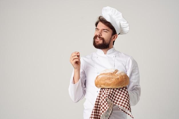 手にパンと明るい背景の男性料理人