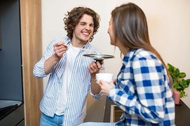 그의 여자가 테이블에 앉아 커피를 마시는 동안 남성 요리는 아침 루틴으로 먹습니다.