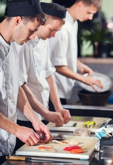 Male cooks preparing sushi. food and drink concept