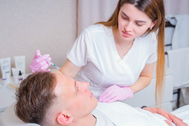 Male cosmetics. good looking man receiving face treatment at luxury spa