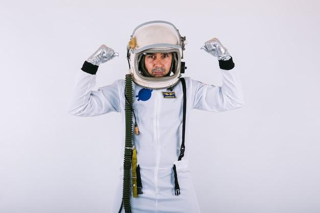 Мужчина-космонавт в скафандре и шлеме, сжимая руки в знак силы, на белом фоне.