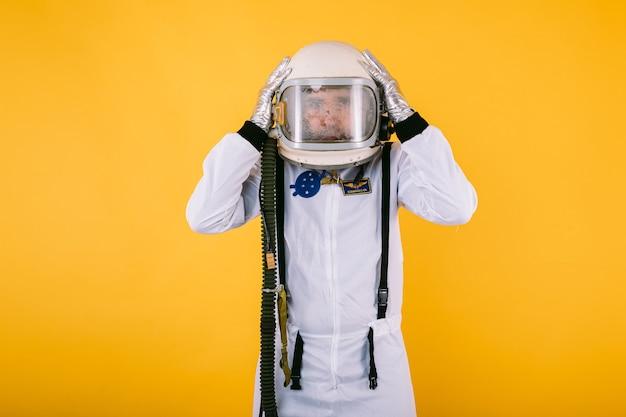 Мужчина-космонавт в скафандре и шлеме, руки на голове, с туманным стеклом, на желтой стене.