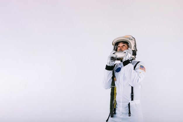 Мужчина-космонавт в скафандре и шлеме держит шлем руками на белом фоне