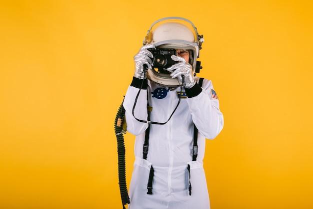 Мужчина-космонавт в скафандре и шлеме, фотографирующий с ретро-камерой, на желтой стене.
