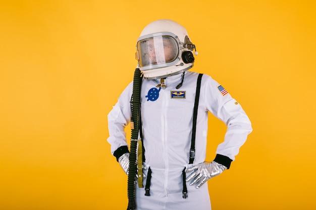 Мужчина-космонавт в скафандре и шлеме с туманным стеклом, руки на талии, на желтой стене.