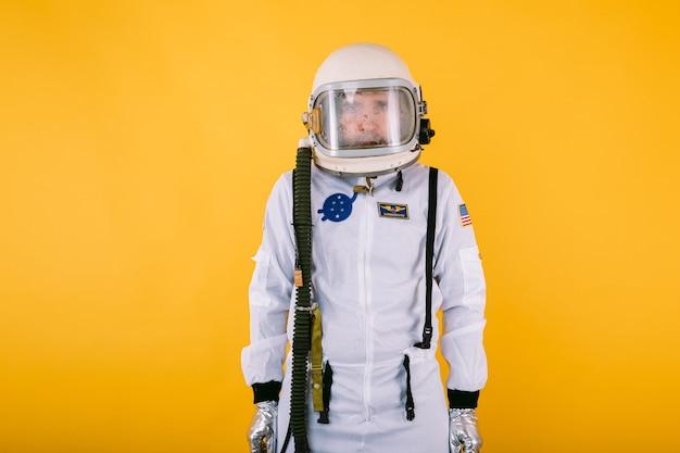 Мужчина-космонавт в скафандре и шлеме с запотевшим стеклом на желтой стене.