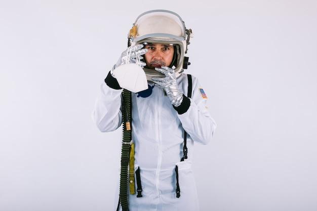 Мужчина-космонавт в скафандре и шлеме, держащий маску fpp2, на белом фоне. covid-19 и концепция вируса