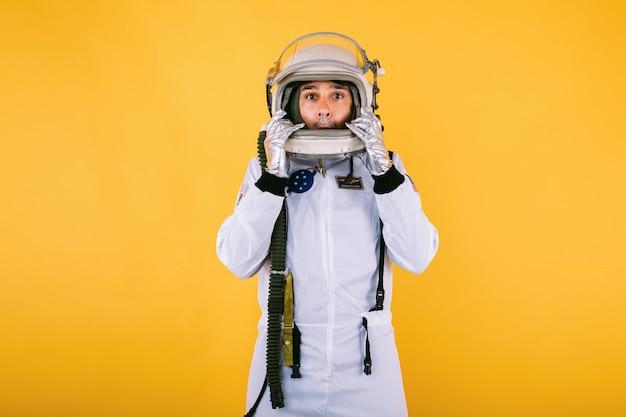 Мужчина-космонавт в скафандре и шлеме, держа шлем руками с жестом удивления, на желтой стене.