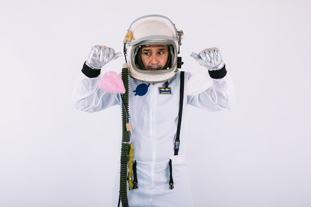 Мужчина-космонавт в скафандре и шлеме, держа две маски fpp2, на белом фоне. covid-19 и концепция вируса
