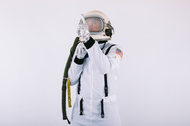 Мужчина-космонавт в скафандре и шлеме, указывая пальцем в небо, на белом фоне.