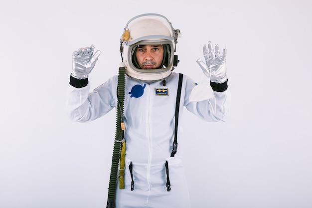 Мужчина-космонавт в скафандре и шлеме, поднимая руки и показывая ладони, на белом фоне.