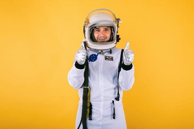 Мужчина-космонавт в скафандре и шлеме, подняв большие пальцы руки, на желтой стене.