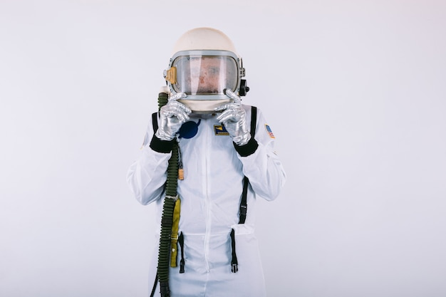 Мужчина-космонавт в скафандре и шлеме, с удивленным лицом, держащим шлем руками, на белом фоне.
