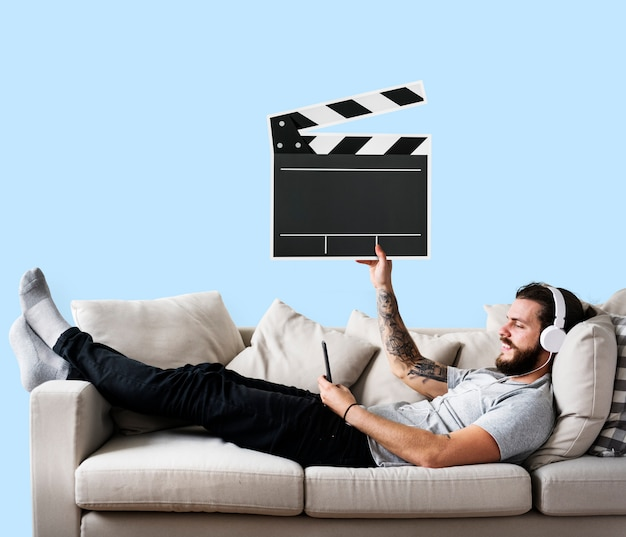 Male on a couch holding a clapper icon