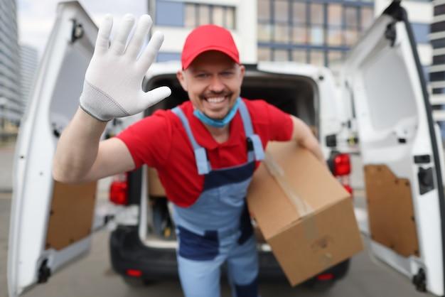Курьер-мужчина держит картонную коробку и машет рукой крупным планом