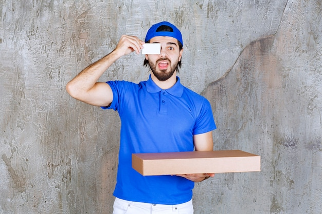 Male courier in blue uniform carrying a cardboard box and presenting his business card.