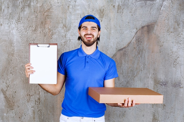 Male courier in blue uniform carrying a cardboard box and presenting the signature list.