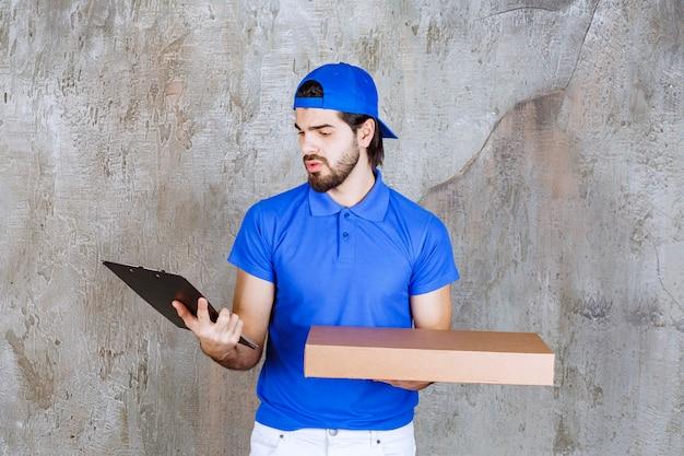 Corriere maschio in uniforme blu che trasporta una scatola di cartone e legge l'elenco dei clienti.