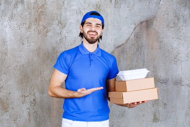 Male courier in blue uniform carrying cardboard and plastic boxes.