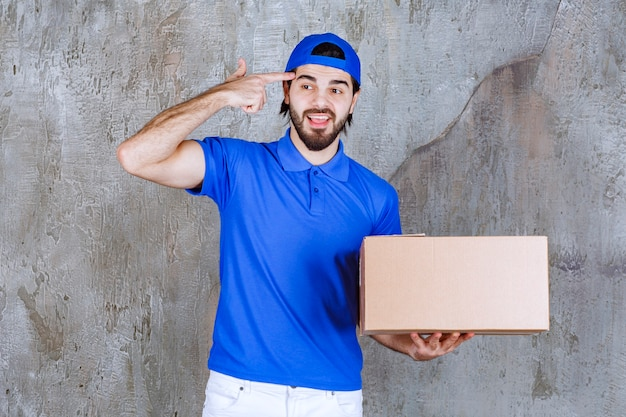 Male courier in blue uniform carrying a cardboard takeaway box, thinking and having a good idea.