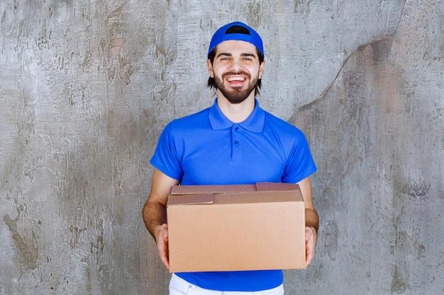 Male courier in blue uniform carrying a cardboard takeaway box .