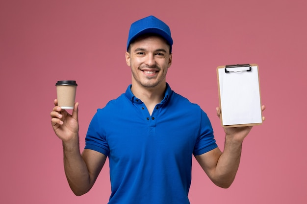 Male courier in blue uniform holding brown coffee cup with notepad on pink, worker uniform service delivery