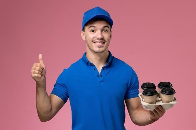 Corriere maschio in uniforme blu che tiene tazze di caffè marroni e sorridente sul rosa, consegna del servizio uniforme operaio