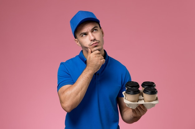 Male courier in blue uniform holding brown coffee cups thinking on pink, worker uniform service delivery