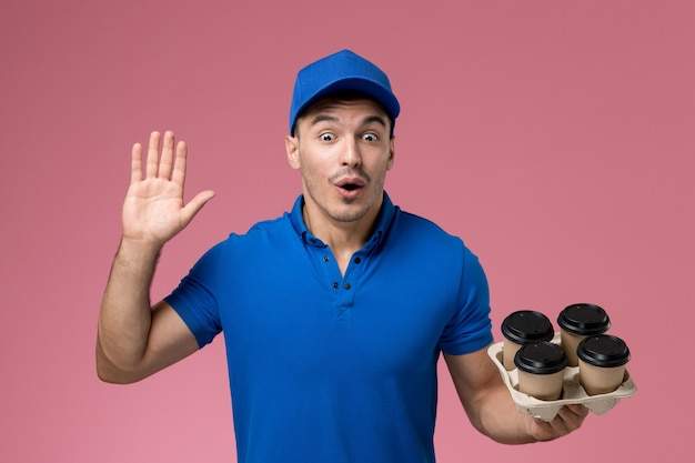 Male courier in blue uniform holding brown delivery coffee cups on pink, uniform job worker service delivery