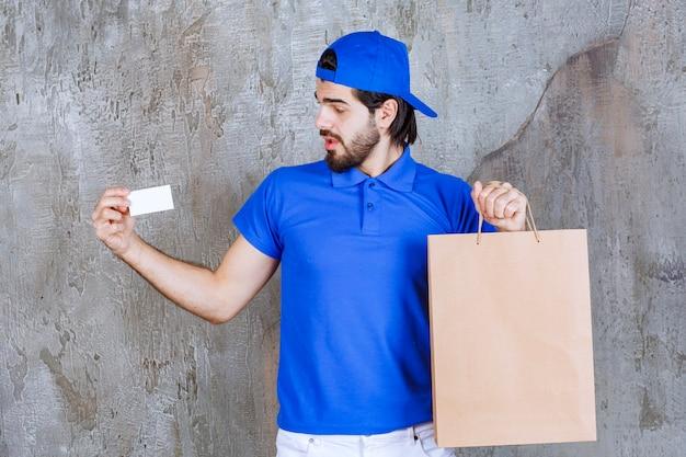 Corriere maschio in uniforme blu che tiene una borsa della spesa di cartone e presenta il suo biglietto da visita.