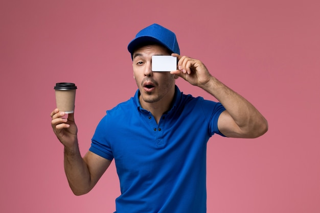Male courier in blue uniform holding coffe and plastic card on pink, uniform service job delivery