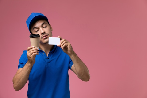 Male courier in blue uniform holding coffee and card on pink, worker uniform service delivery
