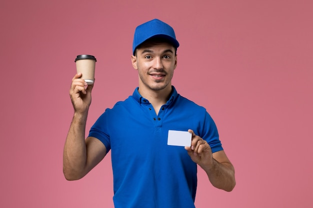 Male courier in blue uniform holding coffee cup and card on pink, uniform service job delivery