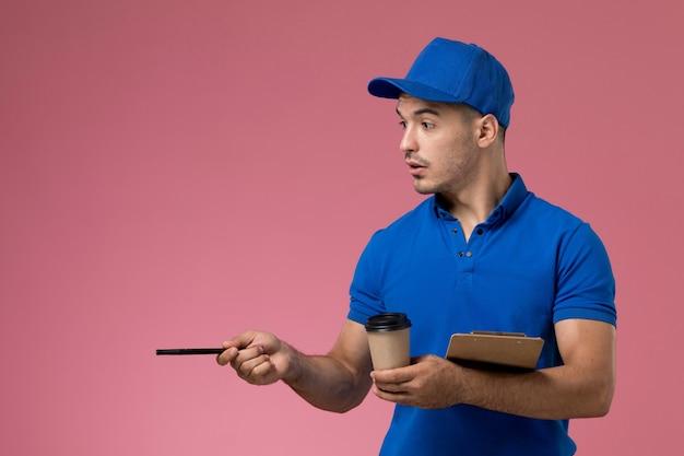 Corriere maschio in uniforme blu che tiene la penna del blocco note della tazza di caffè sul rosa, consegna del servizio uniforme del lavoratore