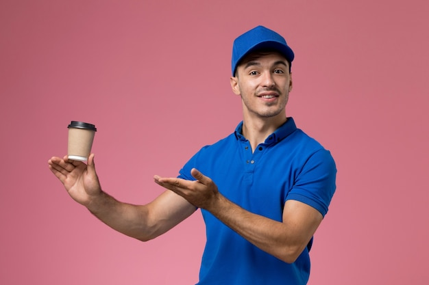 Male courier in blue uniform holding coffee cup posing on pink, worker uniform service delivery