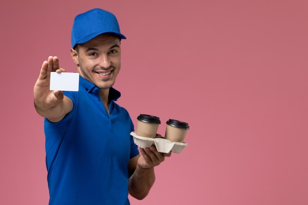 Male courier in blue uniform holding coffee cups and card on pink, job worker uniform service delivery