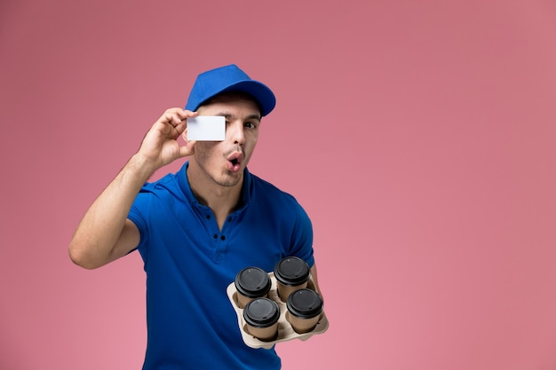 Male courier in blue uniform holding coffee cups and card on pink, worker uniform service delivery