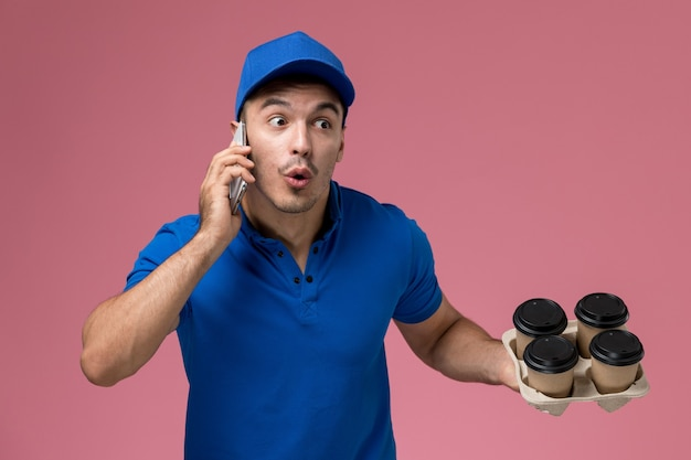 Male courier in blue uniform holding coffee cups and talking on phone on pink, uniform service job delivery