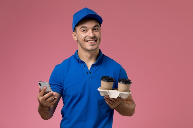 Male courier in blue uniform holding coffee cups using his phone on pink, job worker uniform service delivery