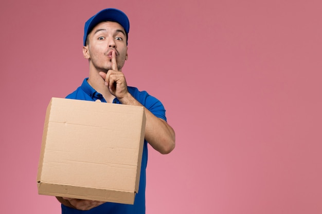 Male courier in blue uniform holding delivery box of food opening it on pink, job worker uniform service delivery