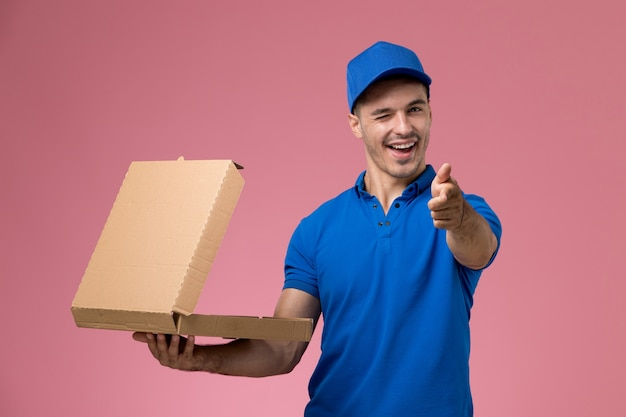 Male courier in blue uniform holding delivery box of food opening it winking on pink, job worker uniform service delivery