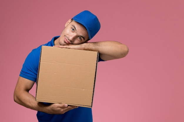 Male courier in blue uniform holding delivery box of food on pink, job uniform service delivery