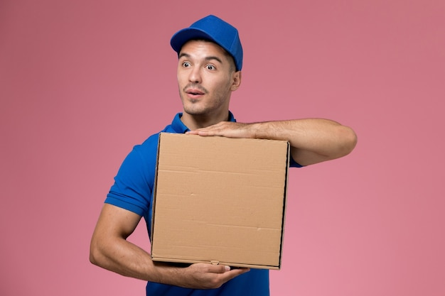 Male courier in blue uniform holding delivery box of food posing on pink, job worker uniform service delivery