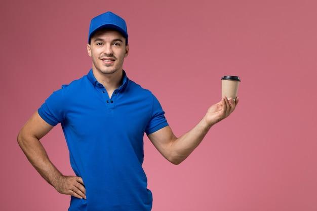 Corriere maschio in uniforme blu che tiene la tazza di caffè di consegna sulla consegna rosa, uniforme del servizio