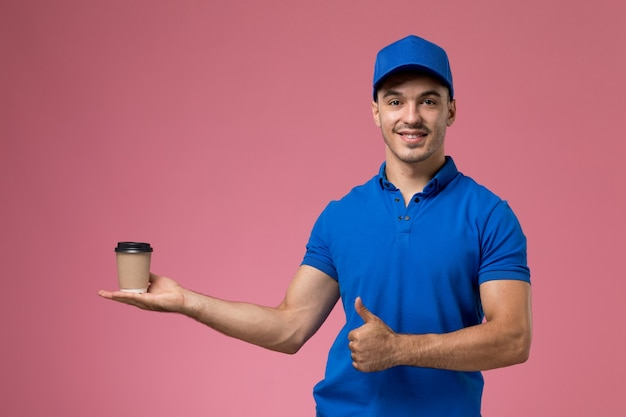 Male courier in blue uniform holding delivery coffee cup and posing on pink, uniform job worker service delivery