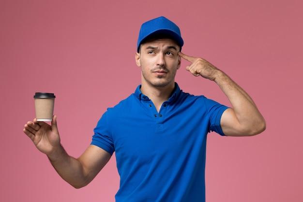 Corriere maschio in uniforme blu che tiene la tazza di caffè di consegna che pensa sulla consegna rosa, uniforme del servizio del lavoratore di lavoro